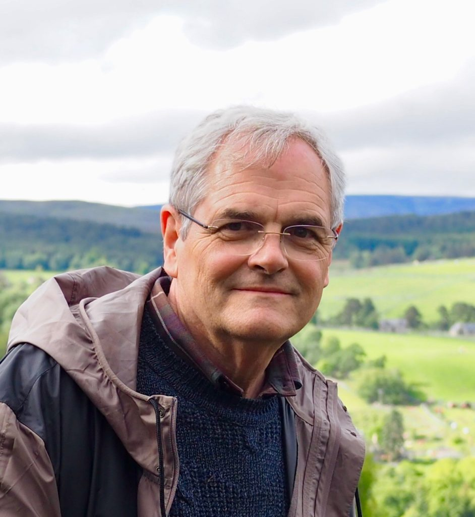 headshot of Allen Tullos, member of the Editorial Board, overlooking a green Scottish landscape on a clear, overcast day