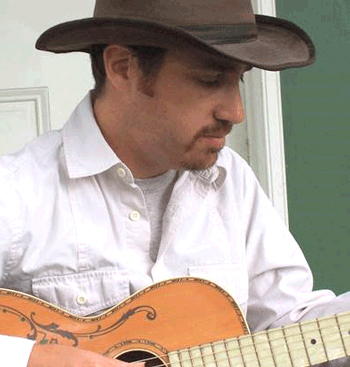 headshot of Gregory Reish, member of the Digital Library Advisory Board, wearing a stetson and playing a guitar in front of a door